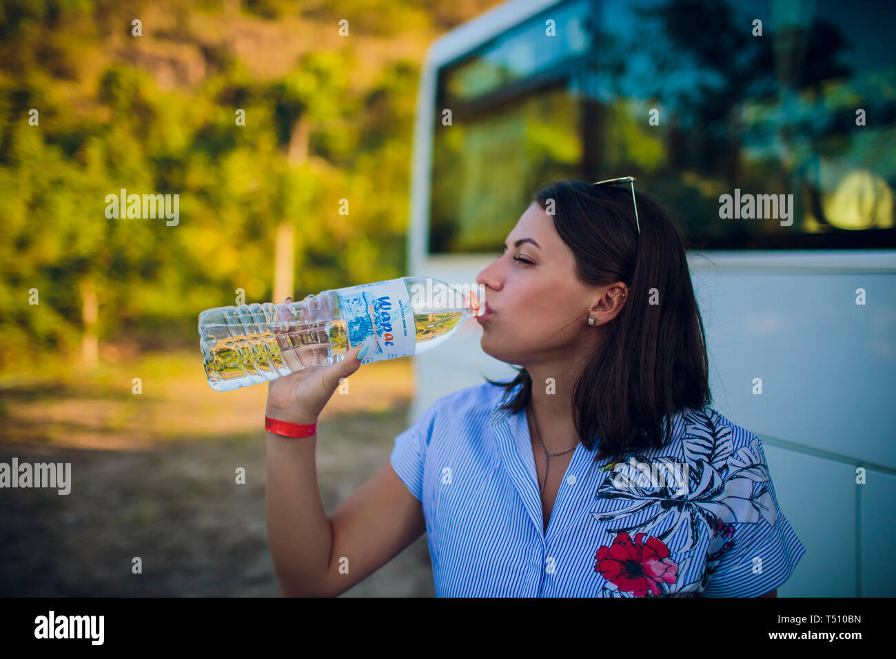 woman drinking water after running outdoors on the background of the bus, tourist. Stock Photo