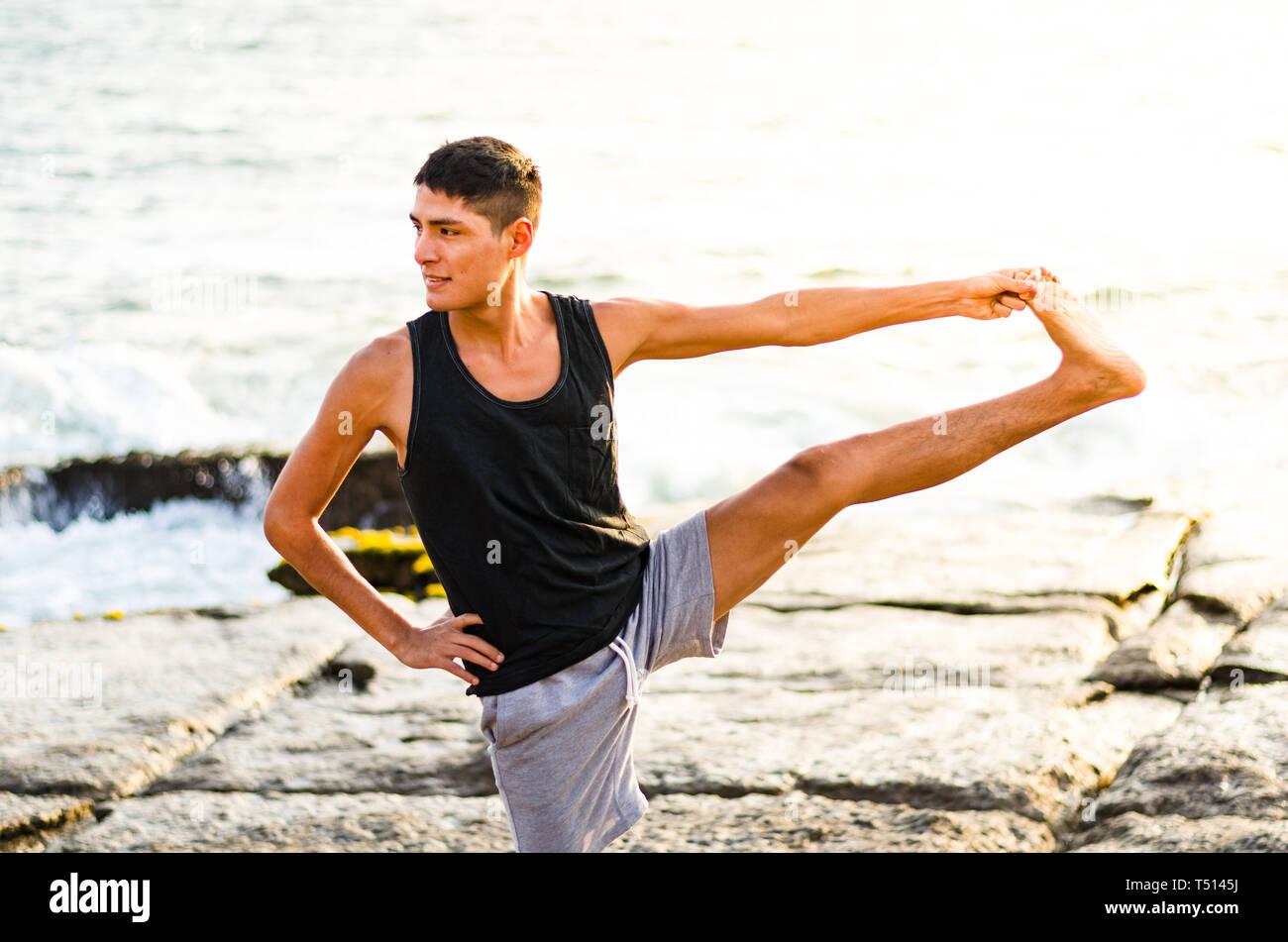 Young man practicing yoga, doing Parivrtta Utthita Hasta Padangusthasana exercise, Twisting Extended Hand to Big Toe pose, working out, yoga - Stock Image