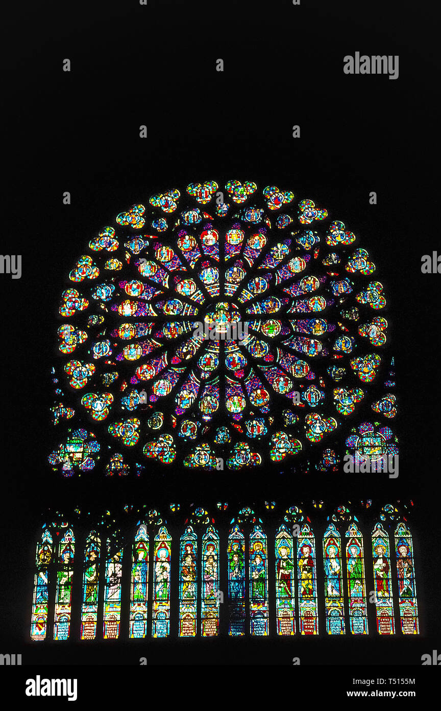 A vertical interior view of one of the three beautiful rose windows in the gothic Notre-Dame de Paris, the famous Catholic cathedral in the French capital that is one of Europe's most popular tourist attractions. This photograph of the large circular stained-glass window was taken before the historic church suffered major damage by a disastrous fire in April, 2019. Rose windows, originally known as wheel windows, depict Biblical scenes or characters in smaller round windows that radiate from the center like wheel spokes or flower petals. Notre Dame's rose windows date to the mid-13th Century. - Stock Image
