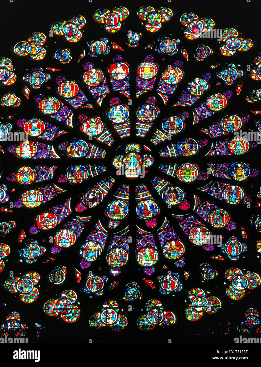A close-up interior view of one of the three beautiful rose windows in the gothic Notre-Dame de Paris, the famous Catholic cathedral in the French capital that is one of Europe's most popular tourist attractions. This photograph of the large circular stained-glass window was taken before the historic church suffered major damage by a disastrous fire in April, 2019. Rose windows, originally known as wheel windows, depict Biblical scenes or characters in smaller round windows that radiate from the center like wheel spokes or flower petals. Notre Dame's rose windows date to the mid-13th Century. - Stock Image
