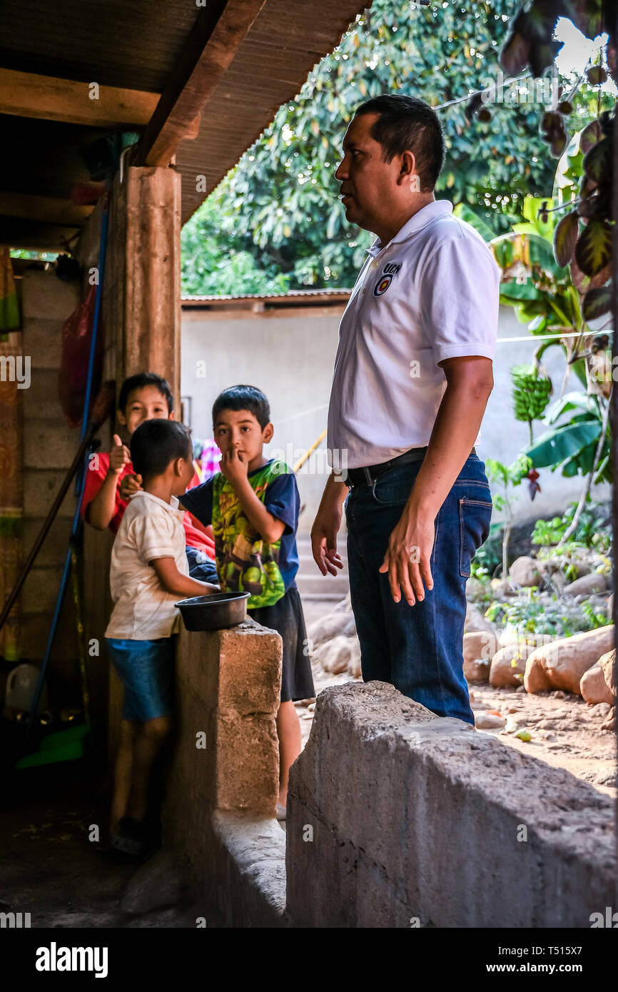 latin man standing with children in background in Guatemalan house Stock Photo