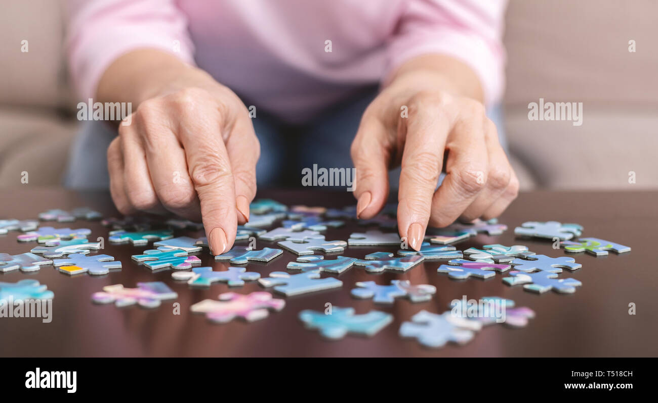 Elderly woman hands doing jigsaw puzzle closeup Stock Photo