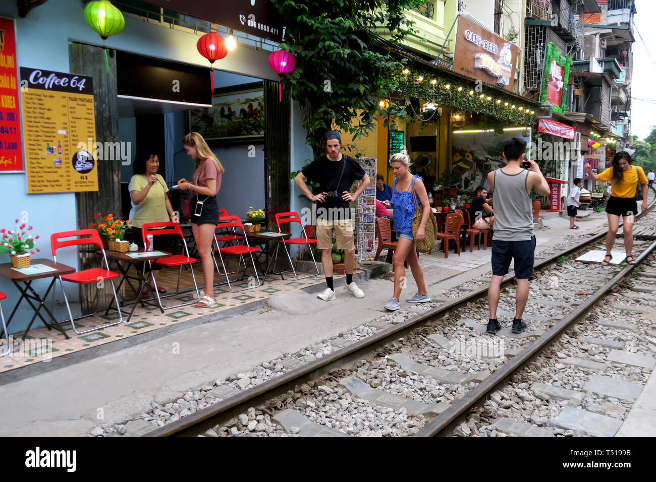 Young tourists at the railway, with cafes as a backdrop as they photograph each other on the rails Old Town, Hanoi, Vietnam - Stock Image
