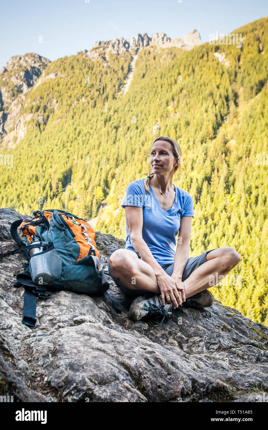 A woman hiker sitting on the edge of a rocky cliff, Little Si Trail, Washington, USA. Stock Photo