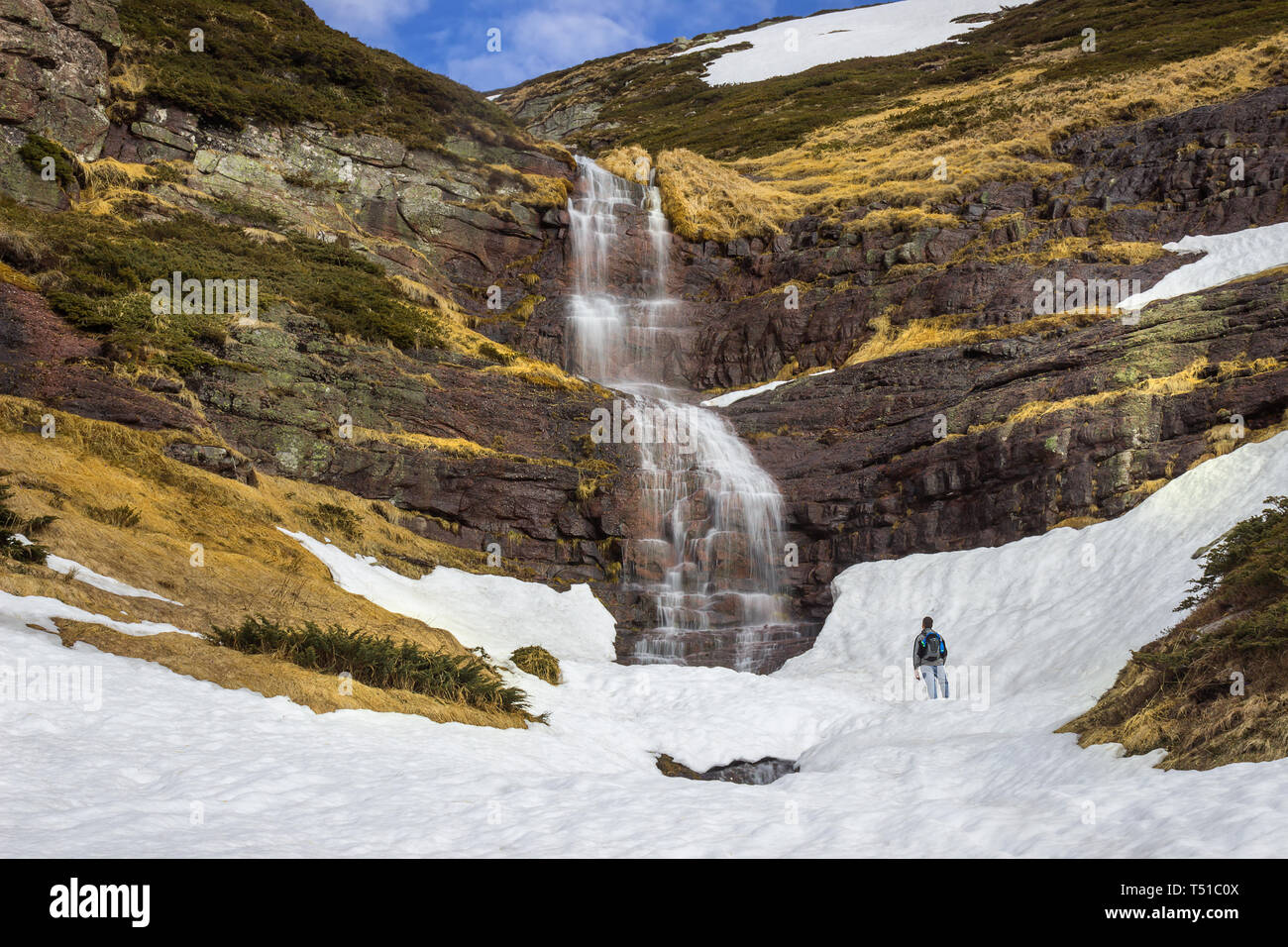 Mountain hiker standing in front of the large, scenic, beautiful waterfall falling from red rocky cliff under the snow - Stock Image
