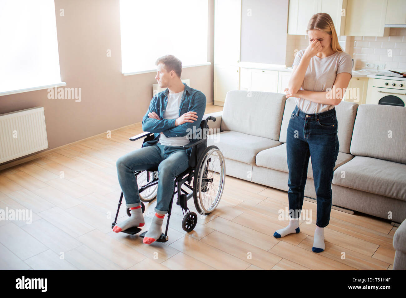 Upset young man with disability on wheelchair. Person with psecial needs. Hands crossed and looking at window. Young woman stand beside and cry - Stock Image