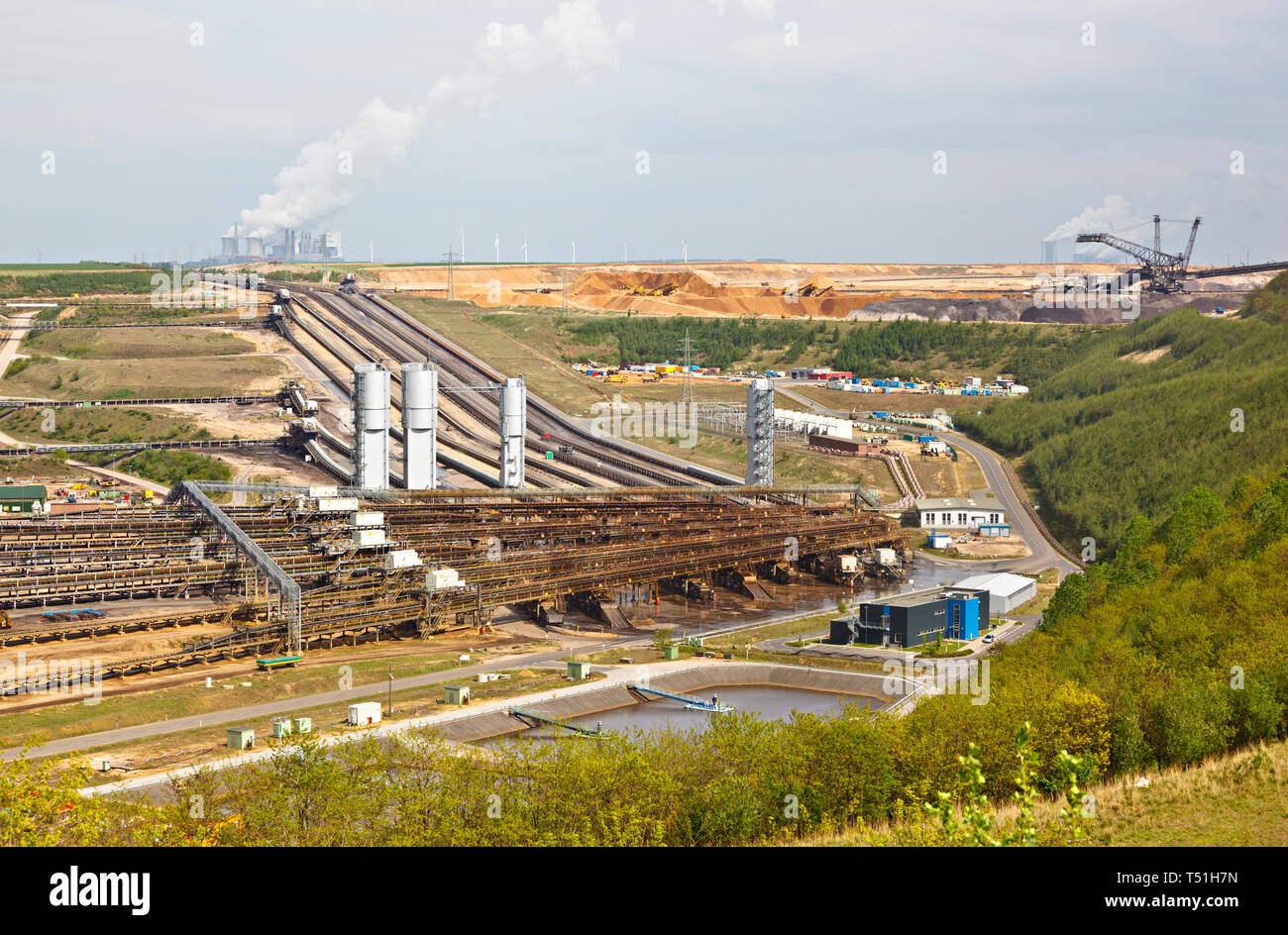 A lignite surface mine with conveyor belts leading to a distant coal power station. Stock Photo