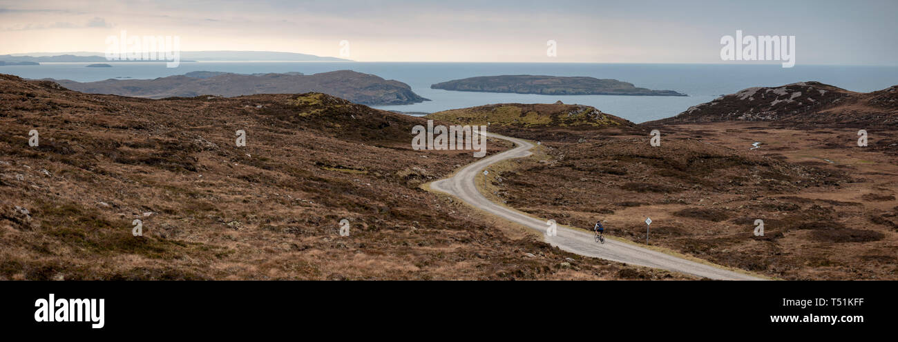 A lone cyclist on the Brae of Achnahaird, with the Summer Isles in the background, west coast of Scotland. - Stock Image