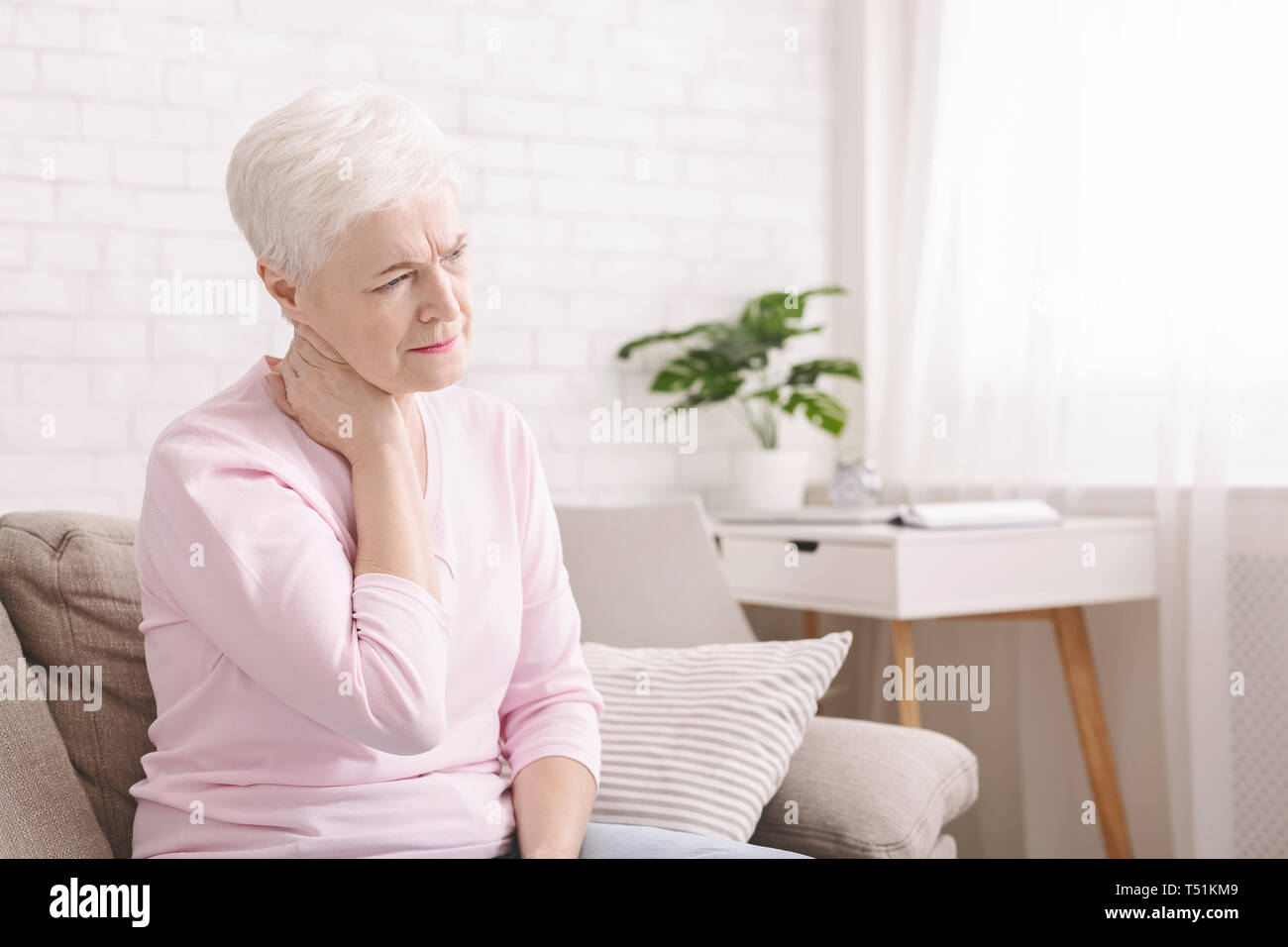 Mature woman suffering from backache at home, massaging neck with hand, feeling exhausted, empty space - Stock Image