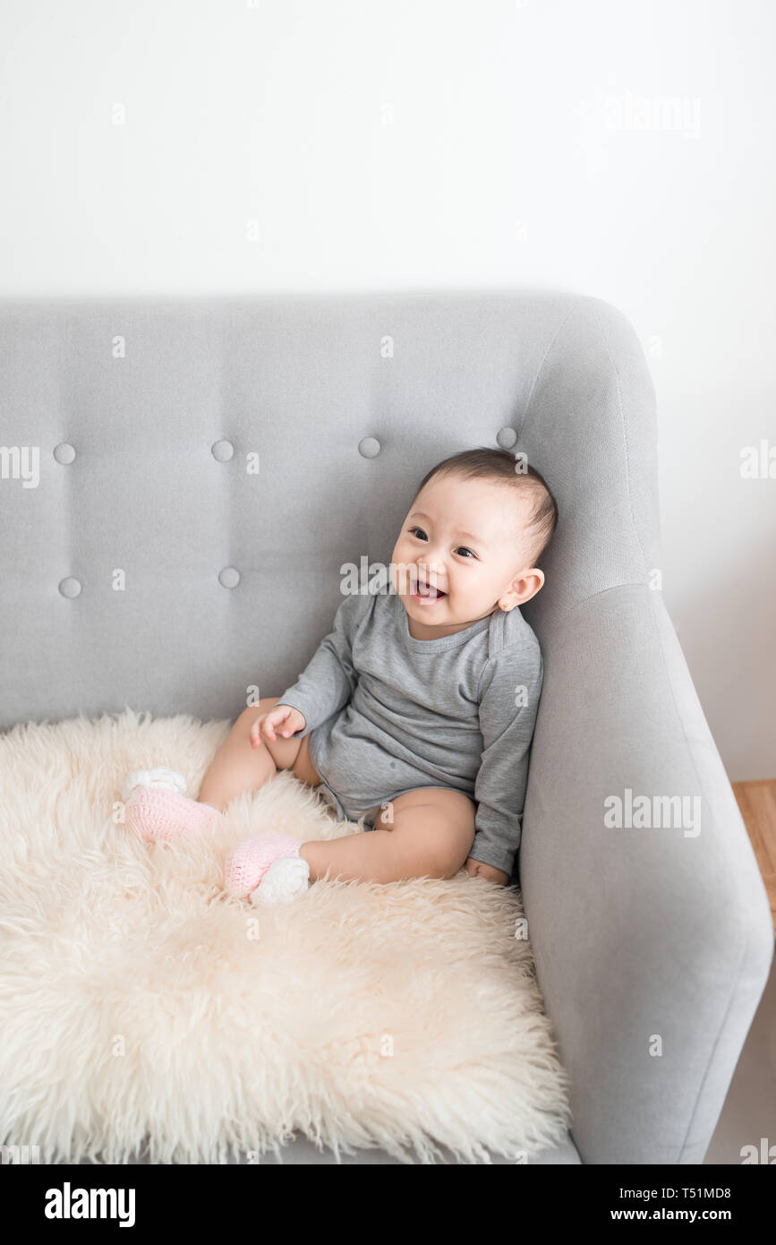 Closeup portrait of cute adorable smiling laughing, baby girl with black eyes sitting on sofa looking away from camera, natural window light, lifestyl - Stock Image