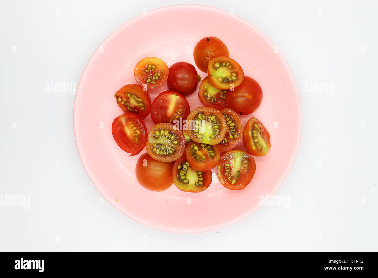 shopped tomatoes in pink dish on white background. - Stock Image