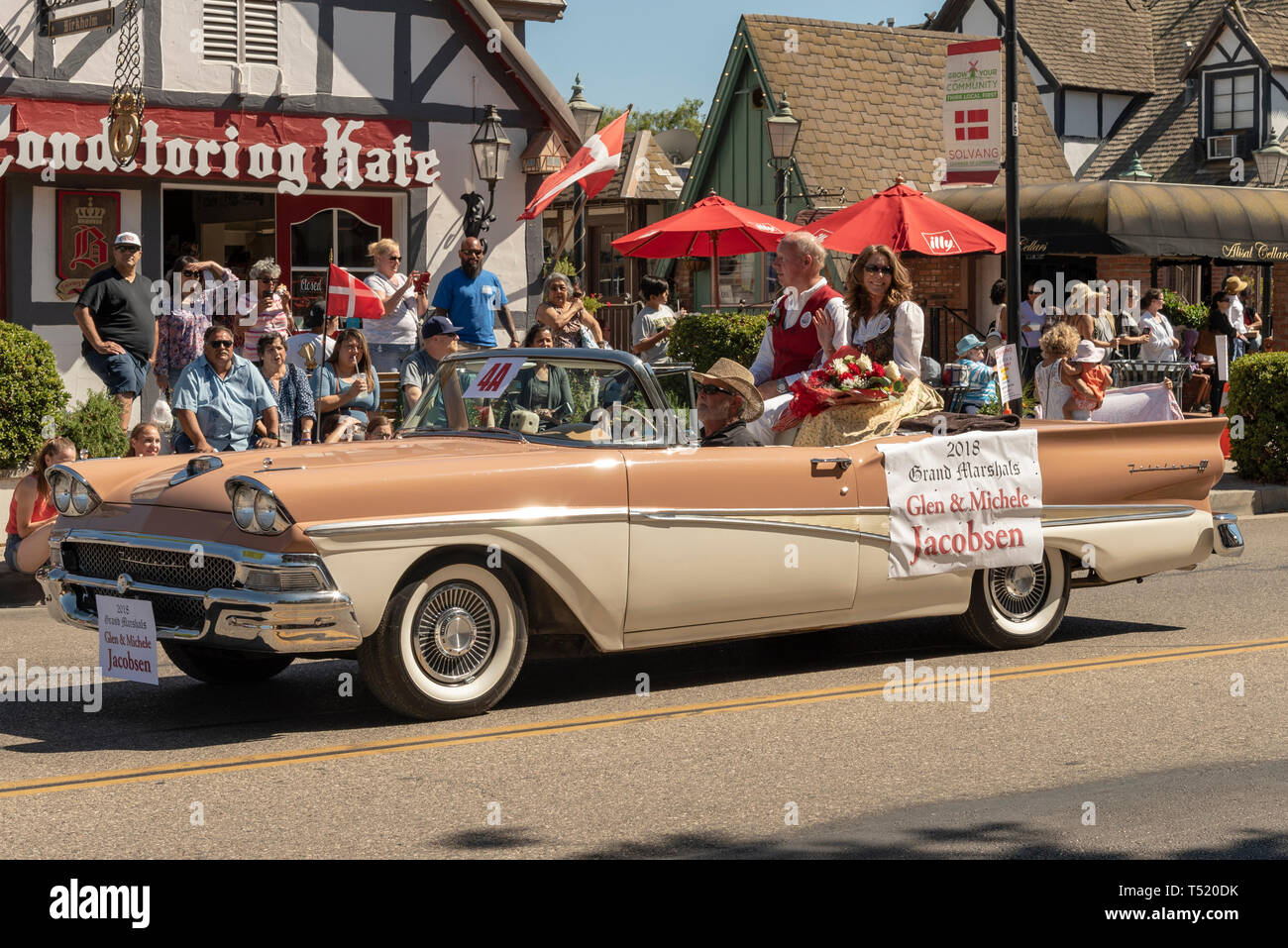 People ridding in two tone antique convertible car in street parade. - Stock Image