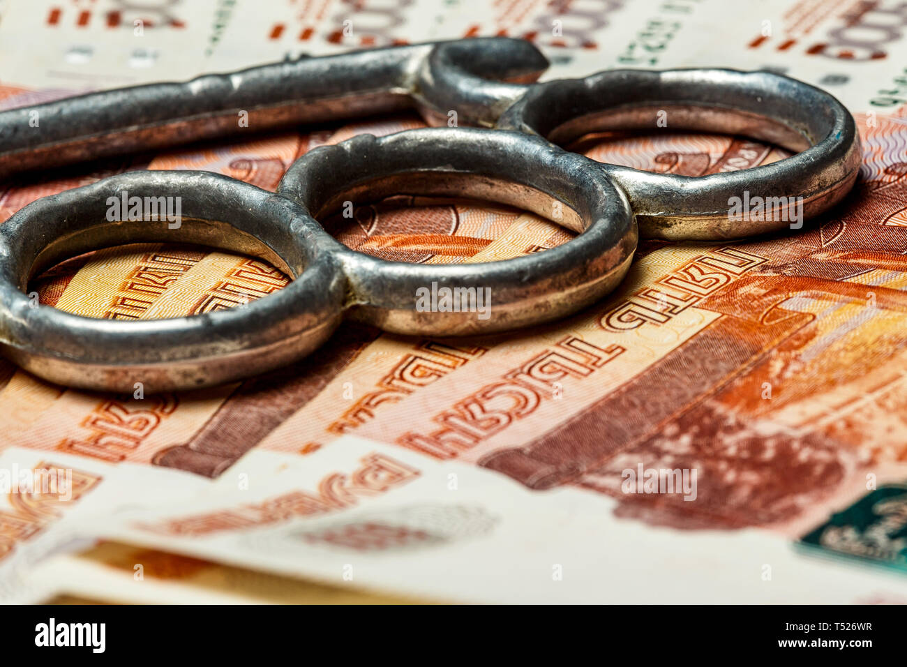 Close up of an iron knuckles Knuckle-duster of crime and pile of paper banknote. - Stock Image