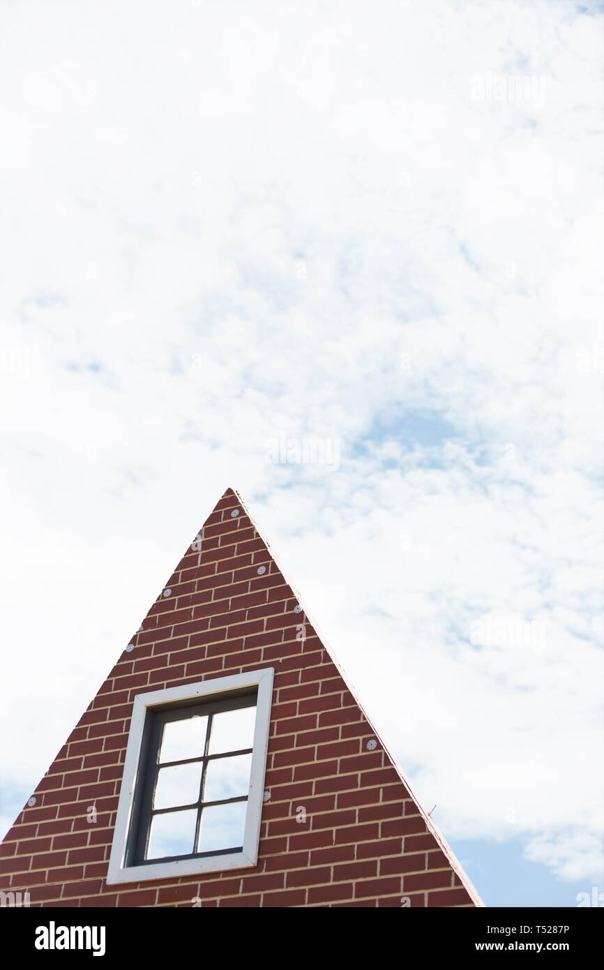 The facade of a brick house, against a partly cloudy sky. - Stock Image