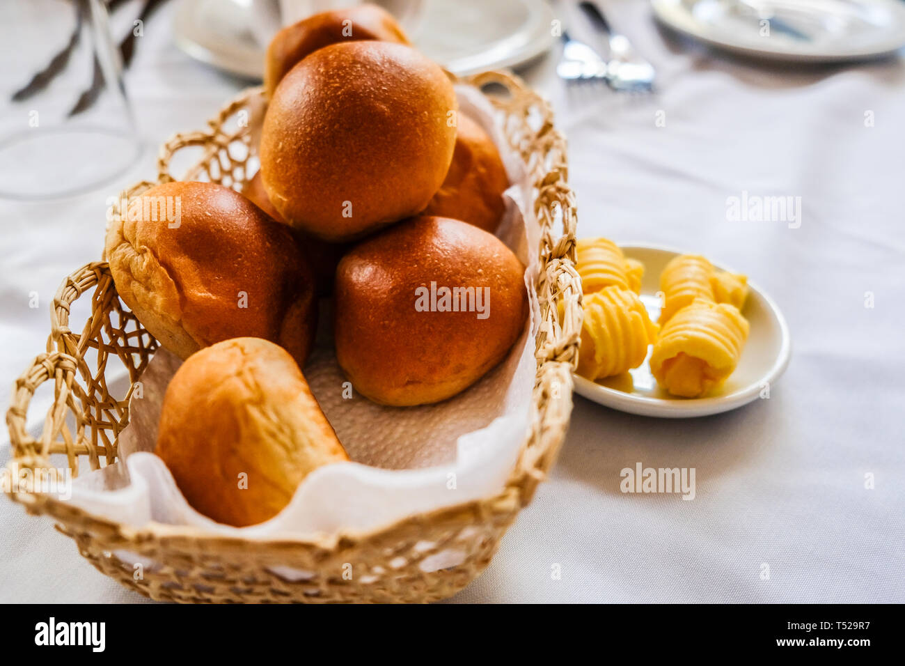Close up of freshly baked bread rolls in basket and butter in small plate on dinning table Stock Photo