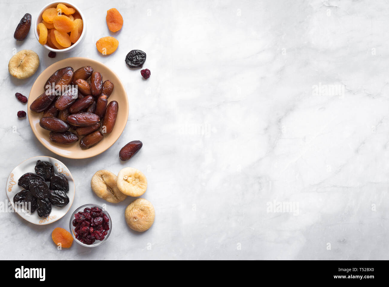 Dried fruits in bowls on white marble background, top view, copy space. Healthy snack - assortment of organic dry fruits. Stock Photo