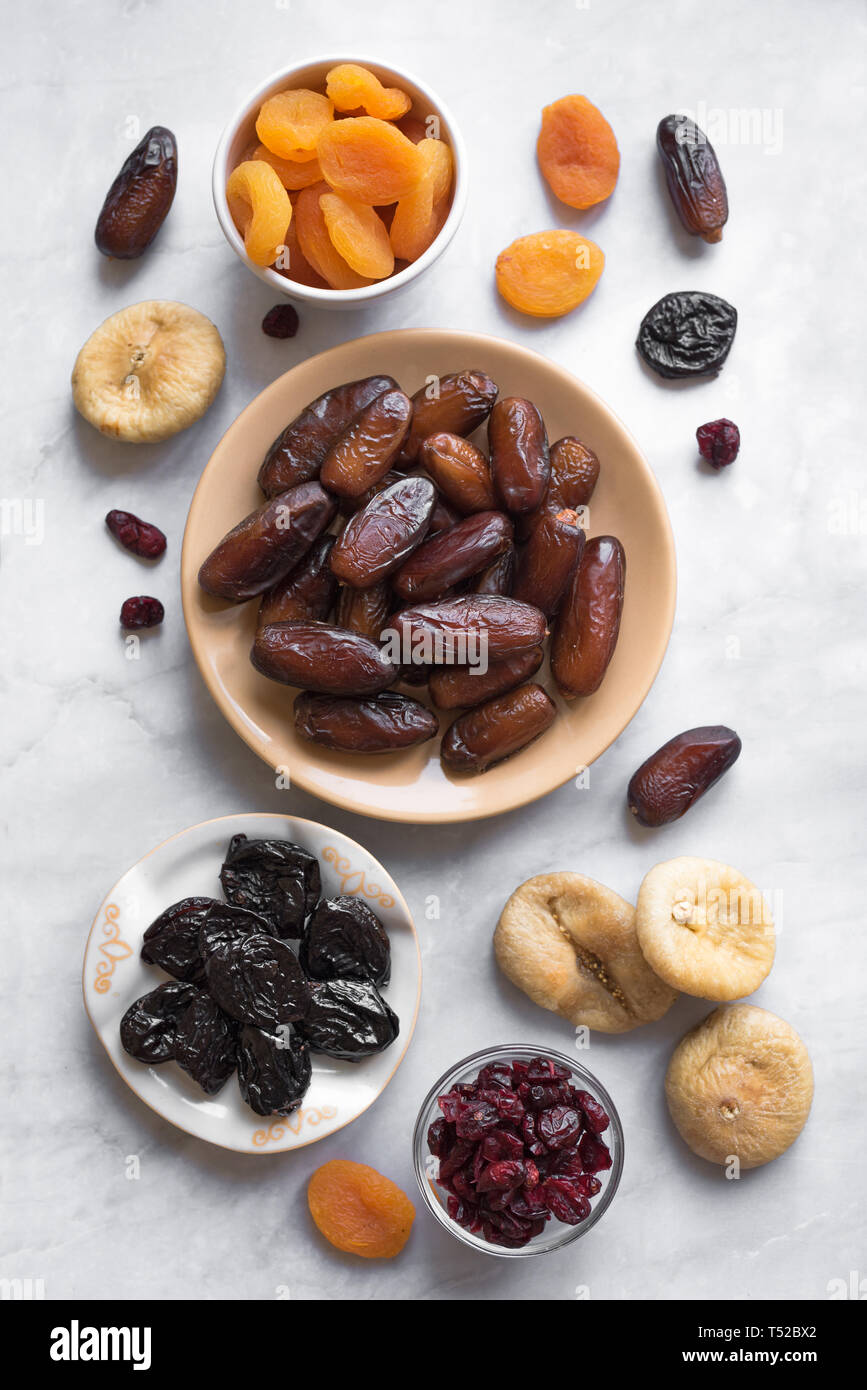 Dried fruits in bowls on white marble background, top view. Healthy snack - assortment of organic dry fruits. Stock Photo