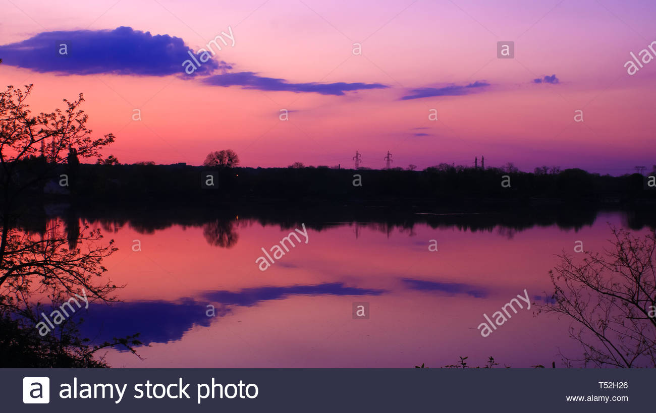 beautiful landscape over the water with symmetry of clouds in colorful sky - Stock Image