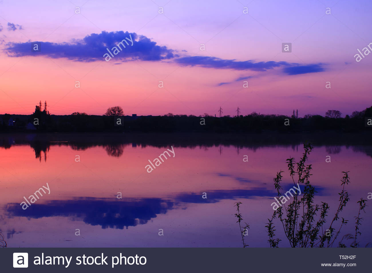 Beautiful reflection of pink and purple clouds in the sea water.  Romantic sunrise very colorful in the countryside - Stock Image