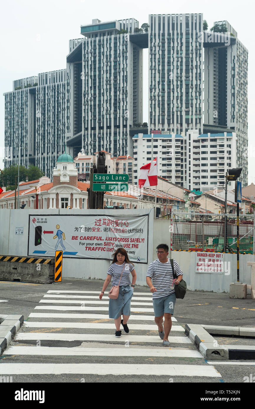 12.04.2019, Singapore, Republic of Singapore, Asia - Pedestrians in Chinatown with The Pinnacle at Duxton housing development in the backdrop. - Stock Image