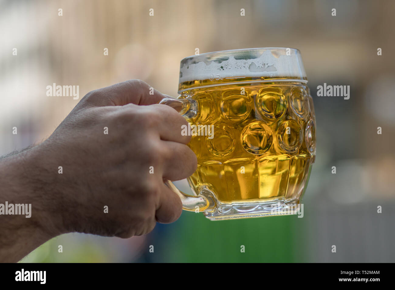 Chilled drink Mug of cold beer. Beer addiction. Alcohol consumption. Harmful addiction. An outstretched hand holds a glass of beer. - Stock Image