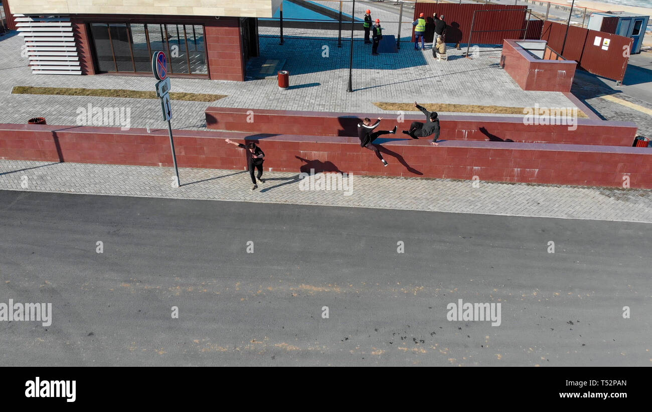 Three athletic young men overcoming obstacles and running on the road. Aerial view - Stock Image