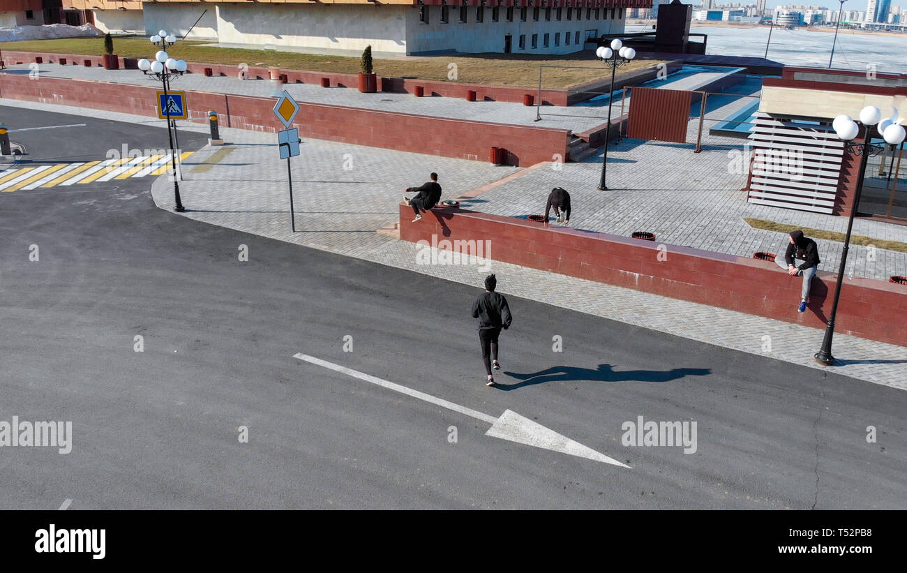 Three young men overcoming obstacles and running on the road. Aerial view - Stock Image