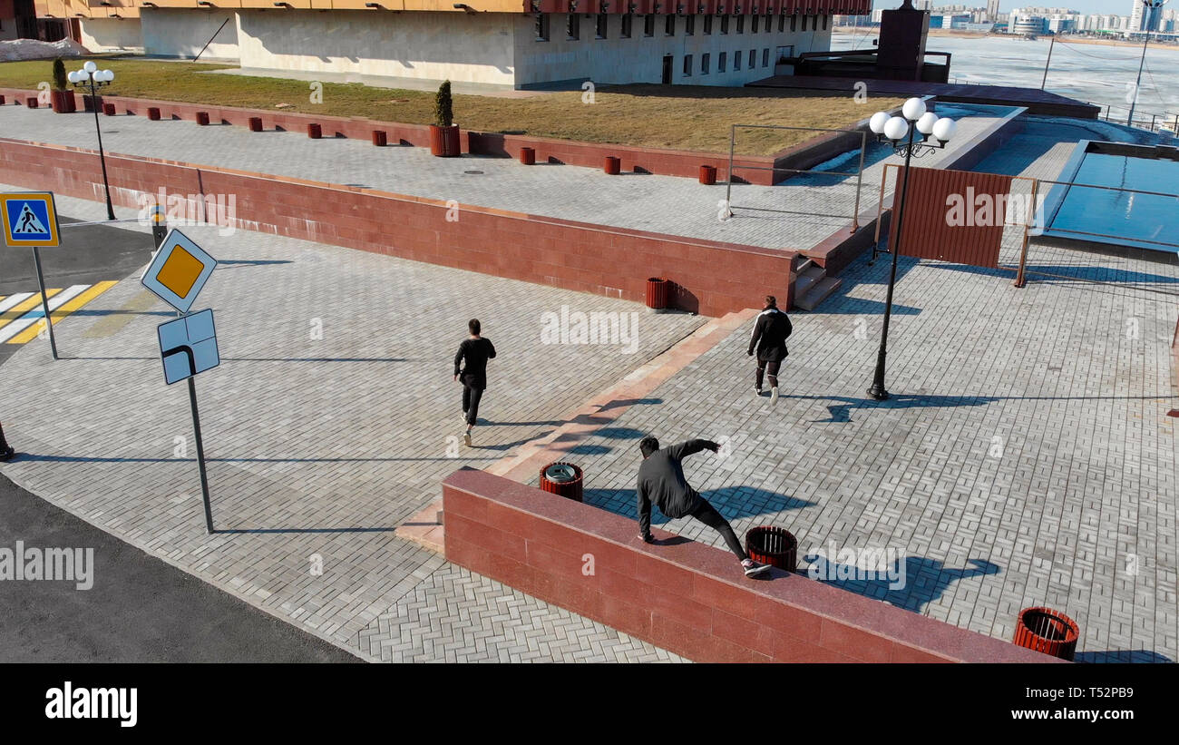 Three young men overcoming obstacles and running on the streets. Aerial view - Stock Image