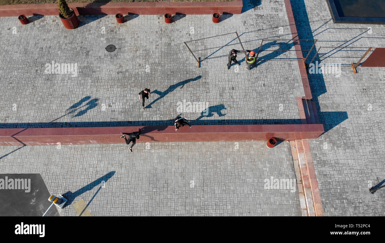 Three young men overcoming obstacles. Aerial view - Stock Image