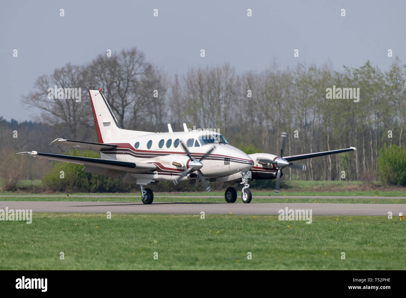 Twin-engined propeller business plane during landing at a small airport - Stock Image