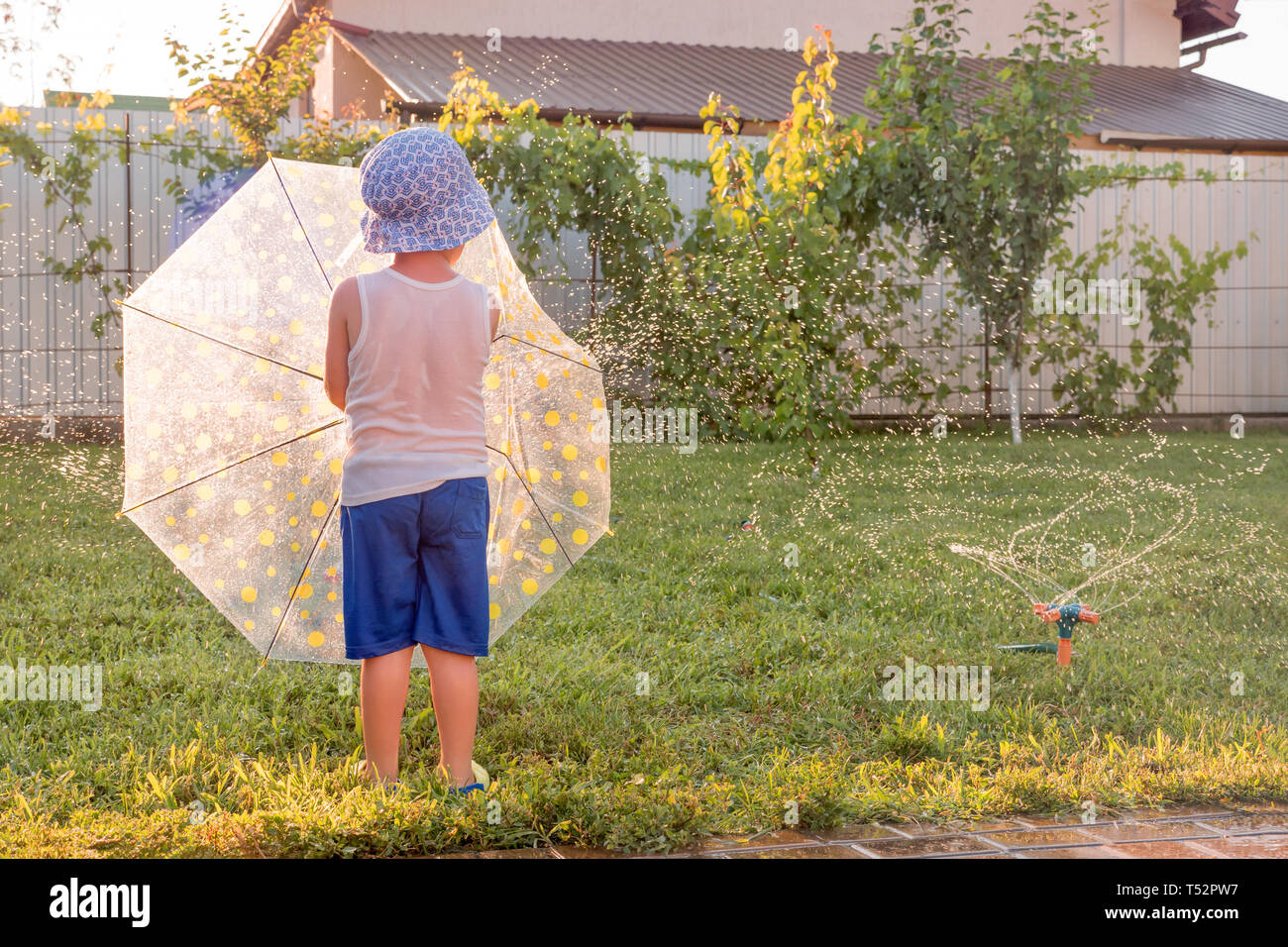 Happy childhood concept. Summer holidays with children. Automatic plant watering system. Preschooler having fun on front yard near watering system - Stock Image