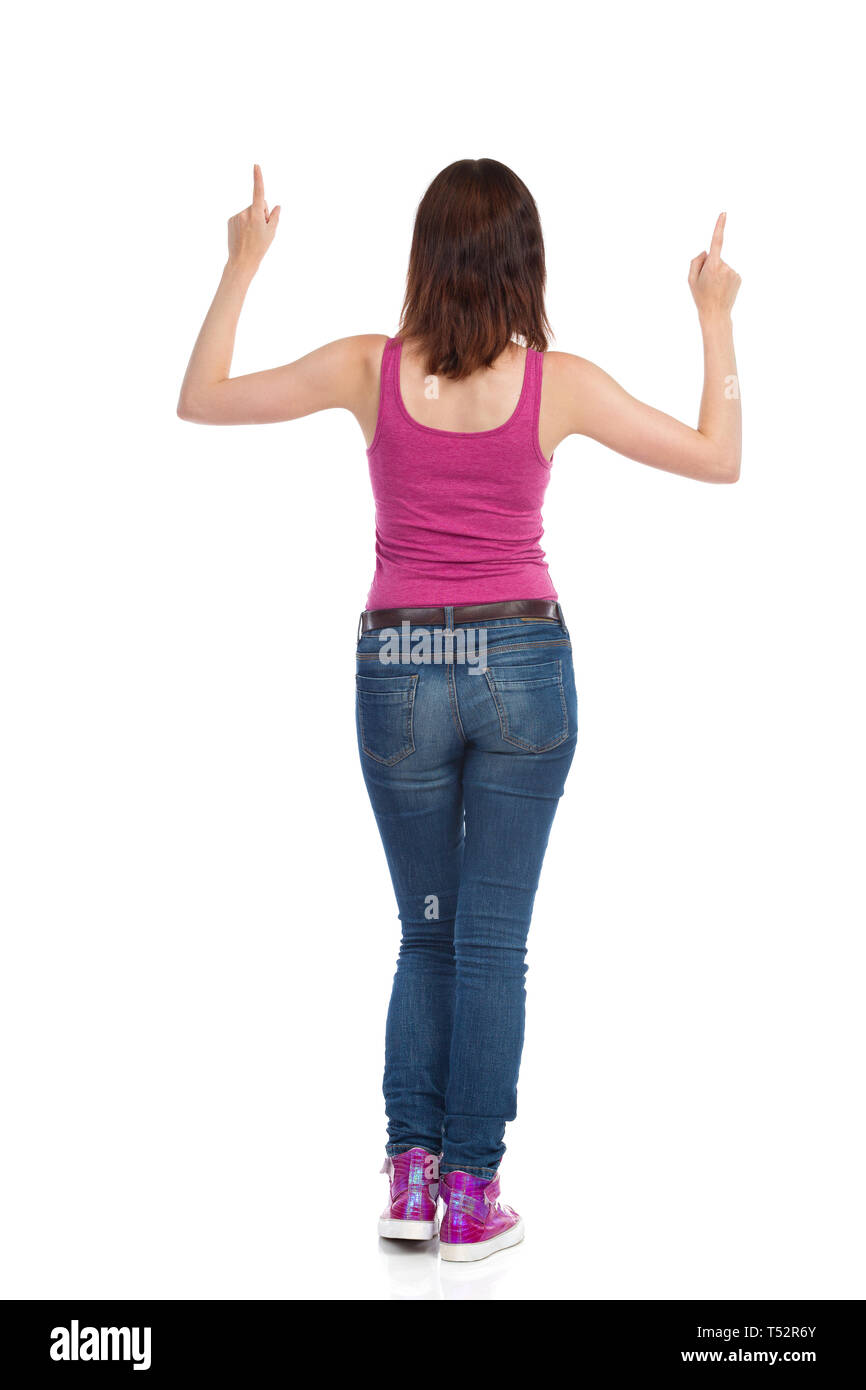 Rear viewv of young woman in magenta tank top, jeans and sneakers, standing and pointing above. Full length studio shot isolated on white. - Stock Image