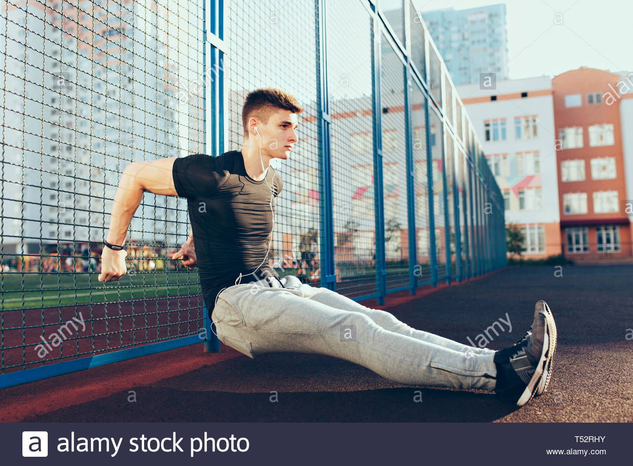 Tense guy with a muscular body at workout training near fence in the