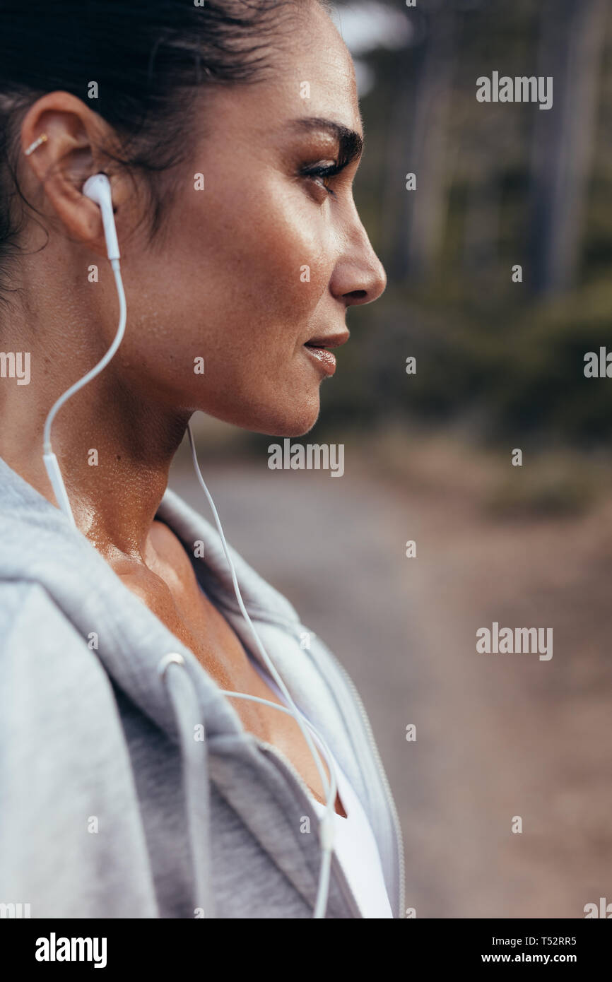 Close up of a female runner with earphones standing outdoors. Woman listening to music during workout outdoors in morning. - Stock Image