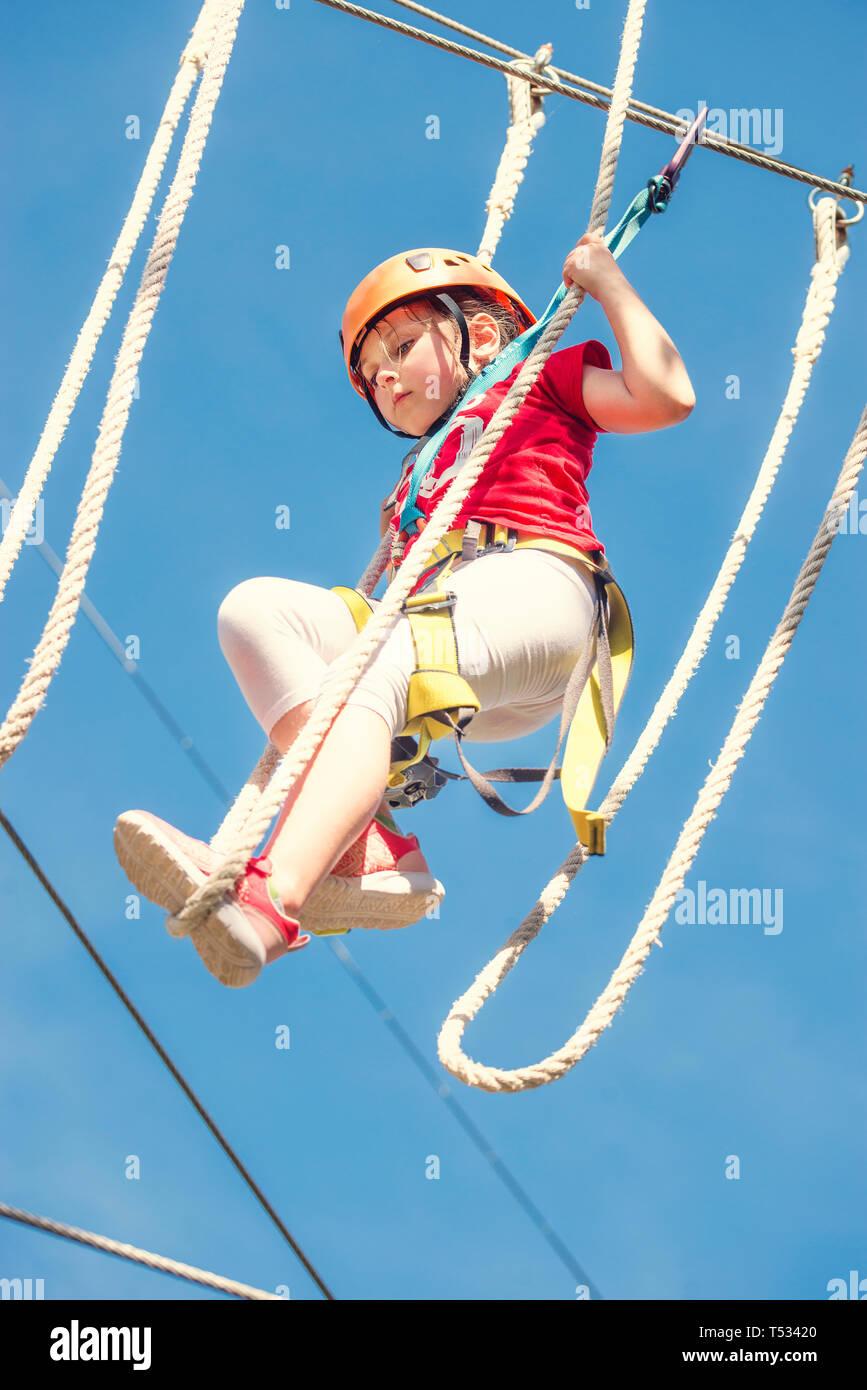 Little brave caucasian girl at outdoor treetop climbing adventure park Stock Photo
