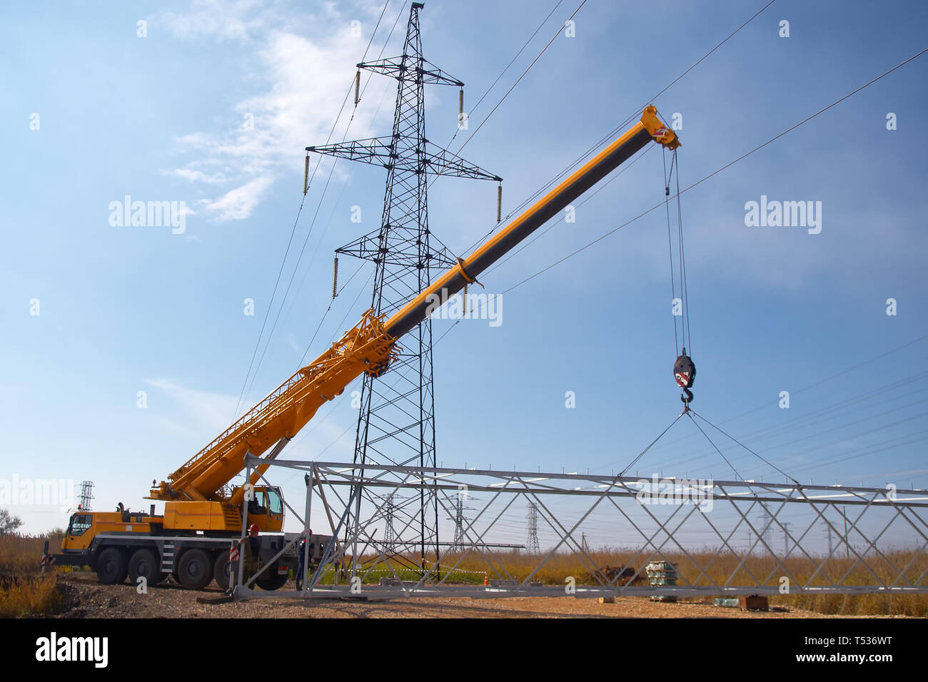 A crane installs a high voltage power line in an industrial
