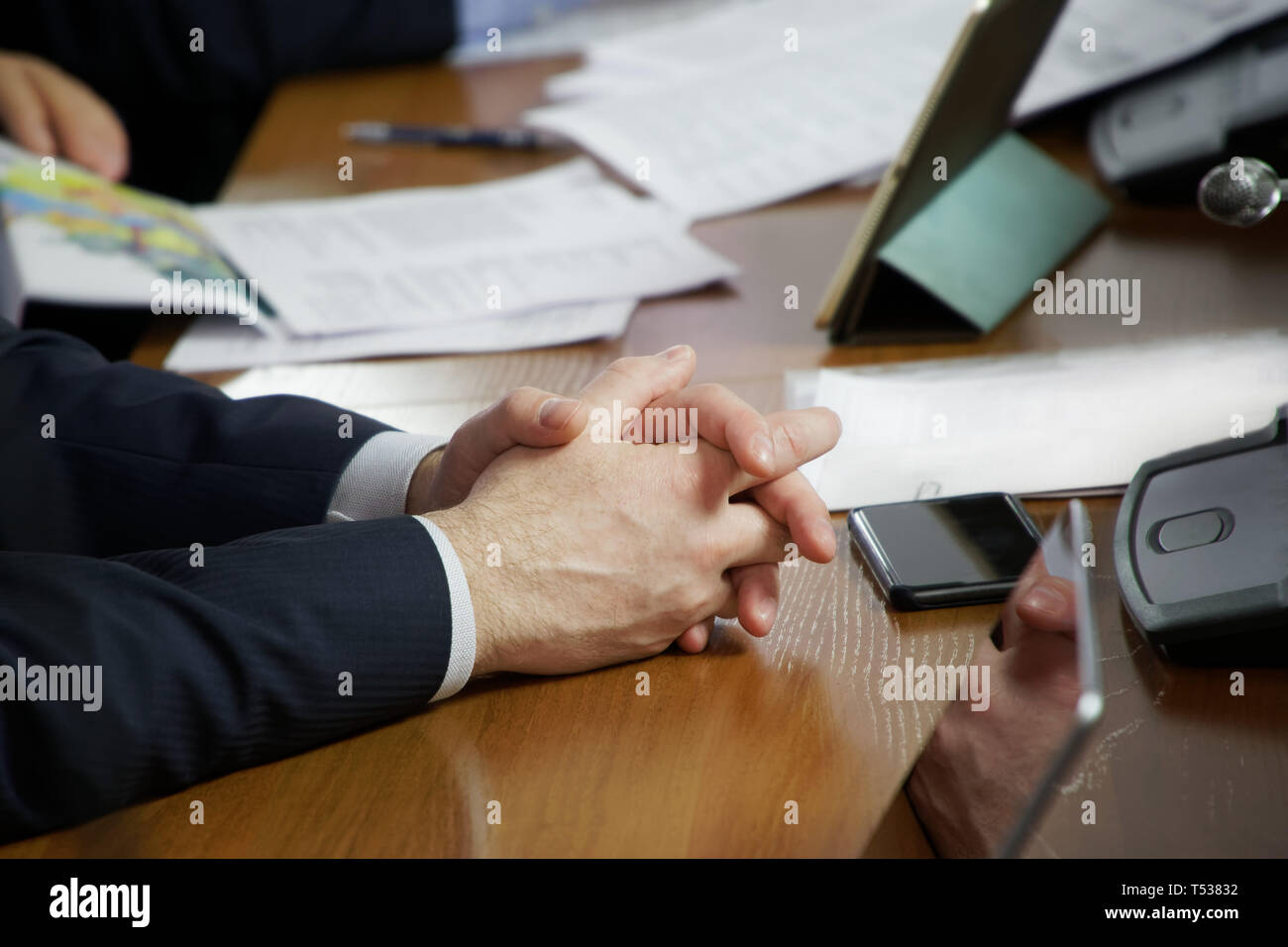 Hands of a person sitting at a table during a business meeting. Job responsibilities - Stock Image