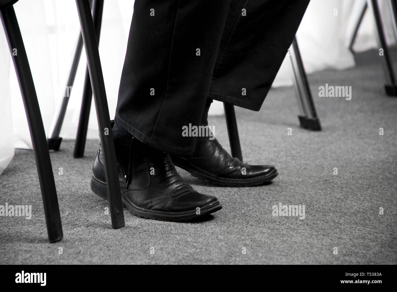 The legs of a man waiting in an office chair in the corridor. Job responsibilities. - Stock Image