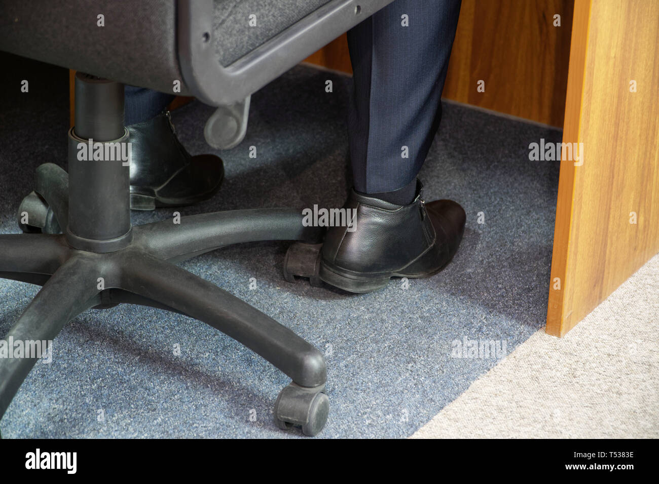 The legs of a man sitting in an office chair while on duty at work. Job responsibilities - Stock Image
