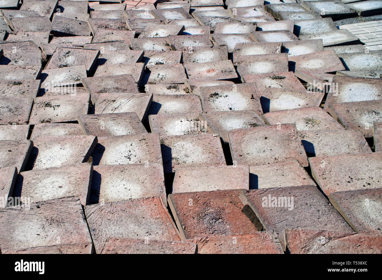 Old worn paving slabs during dismantling from a city street. Reconstruction. Urban economy. - Stock Image