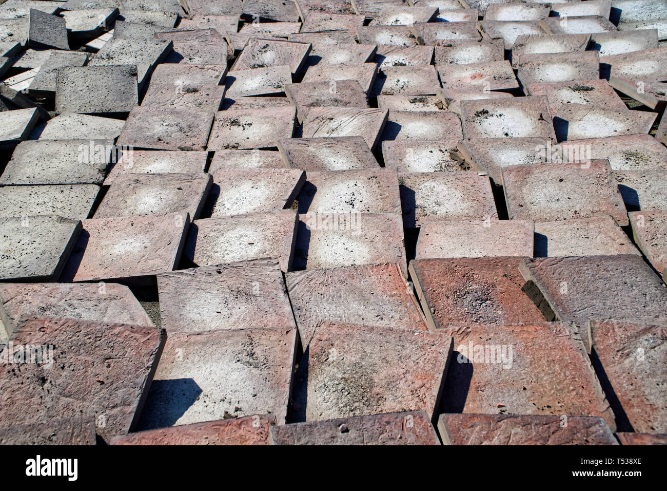 Old worn pavement tiles after dismantling from the streets of the city. Urban economy. Chip - Stock Image