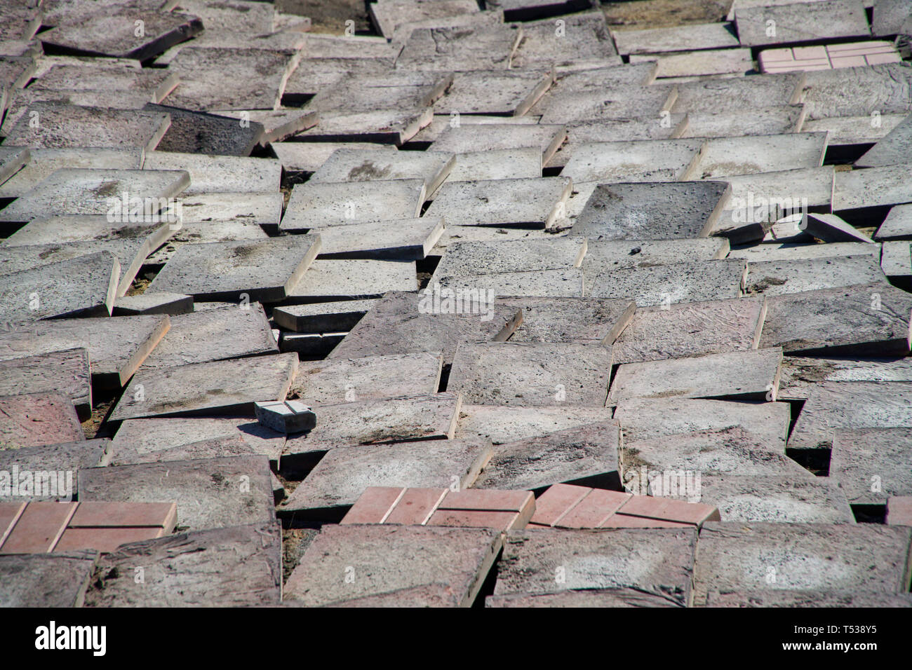 Old worn pavement tiles in the process of dismantling and replacement. Urban economy. - Stock Image