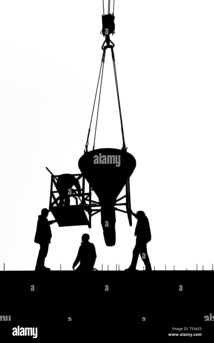 Silhouettes of workers pouring a concrete wall using a crane with a large bucket on a white background - Stock Image