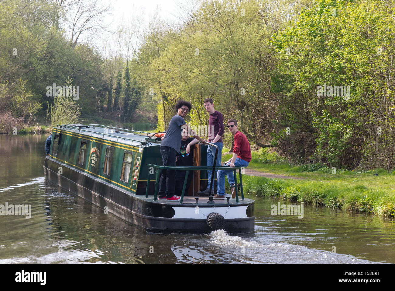 Group of British lads out together in a narrowboat travelling along a UK canal. Boating holiday in the spring sunshine. Having fun in the sun. - Stock Image