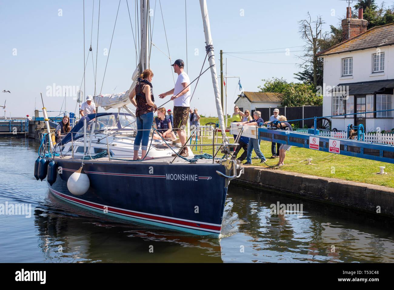 Yacht named Moonshine in Heybridge Basin lock, Essex, UK, entering the Chelmer and Blackwater navigation. People operating the lock gate. Sea lock - Stock Image