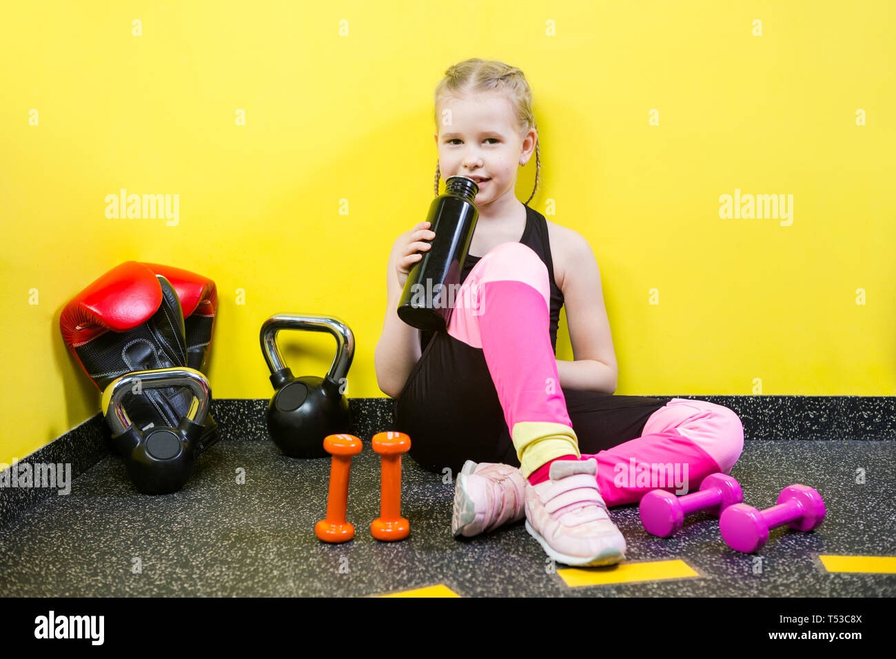 Theme sports and health children. Little Caucasian girl sits resting break floor gym holds hand bottle, drink water thirst. Athlete dumbbell - Stock Image