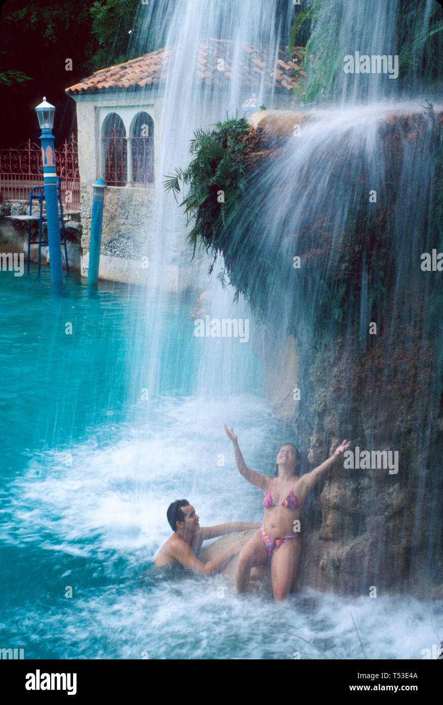 Coral Gables Miami Florida Venetian Pool former quarry visitors under waterfall - Stock Image