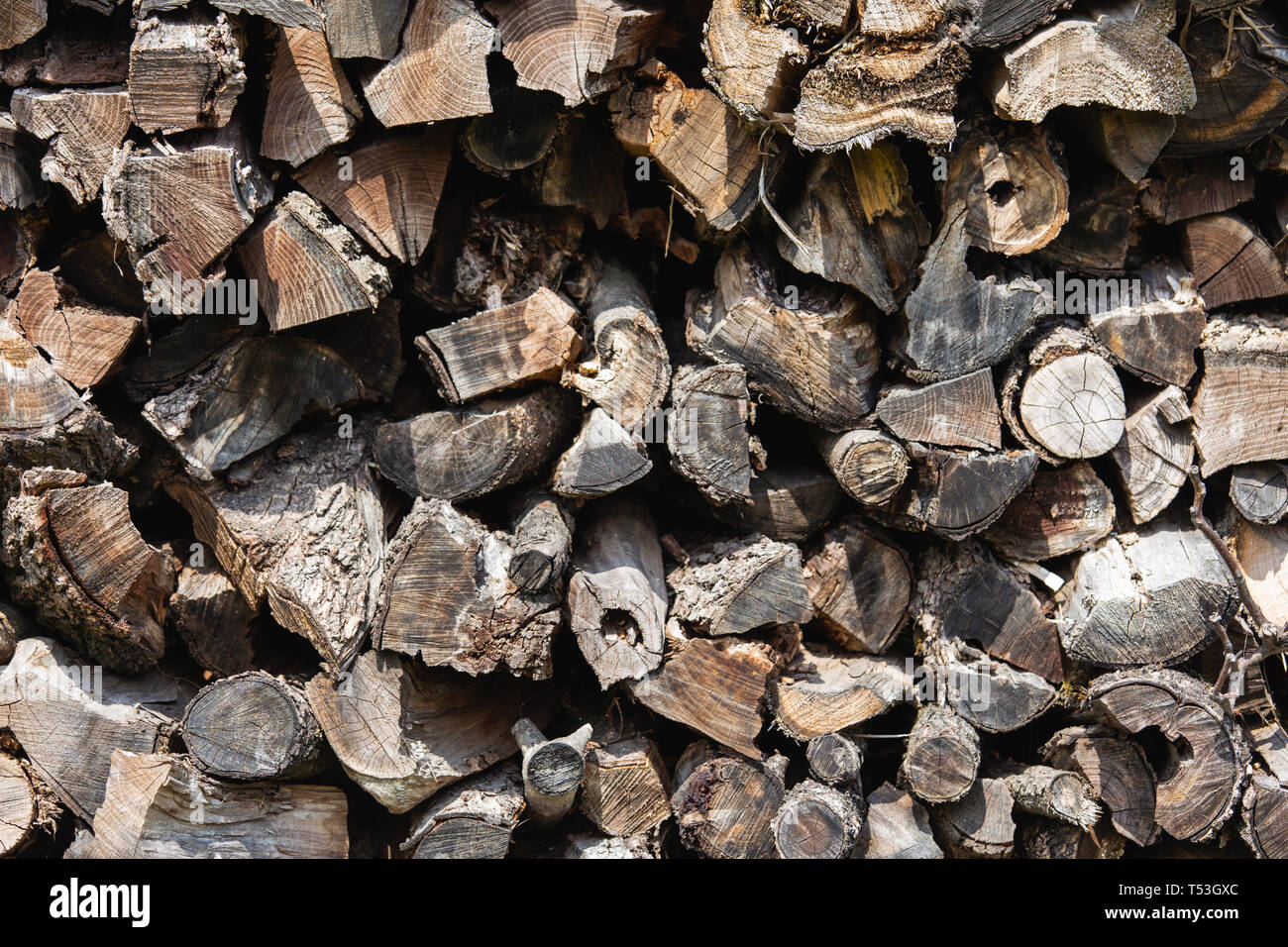Background from stacked old brown stab wooden logs - Stock Image