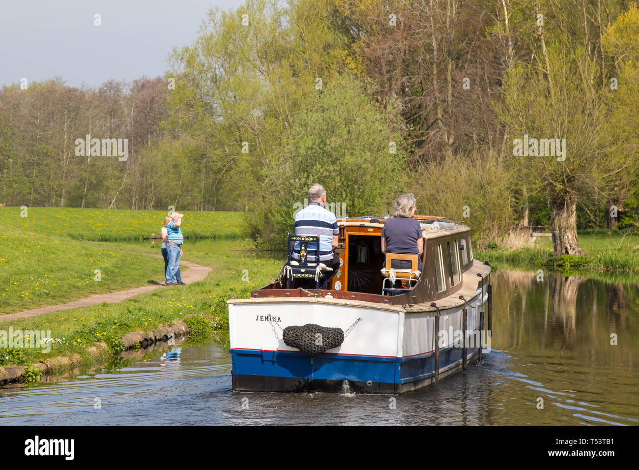 Rear view of retired couple on board their UK canal boat enjoying the British canals on a sunny morning in spring. - Stock Image