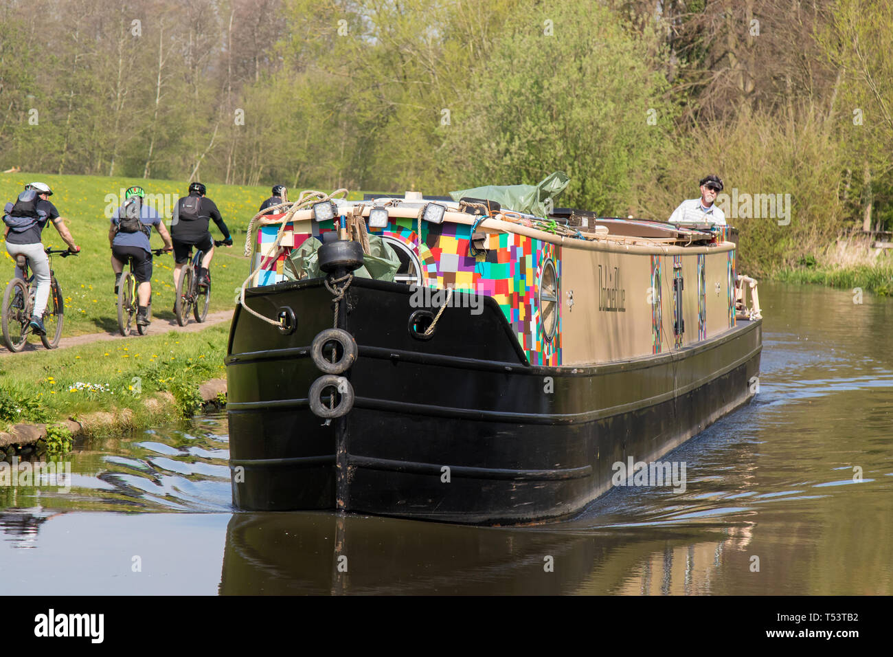 Landscape, close up of oncoming narrowboat travelling on UK canal in spring sunshine, single man steering at rear. Cyclists ride along canal towpath. - Stock Image